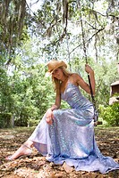 Portrait of young blonde woman in evening gown and cowboy hat sitting on swing outdoors