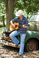 Young cowboy playing guitar and leaning on vintage truck outdoors