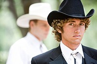 Portrait of two young cowboys in cowboy hats outdoors