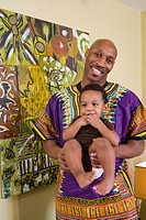Portrait of happy African American father dressed in traditional African attire holding son in living room indoors