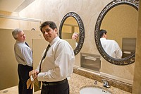 Two multi_ethnic businessmen standing in office bathroom, smiling