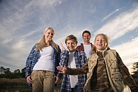 Portrait of young happy family standing on pier by river, high angle view