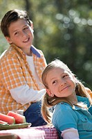Happy boy and girl sitting at picnic table outdoors