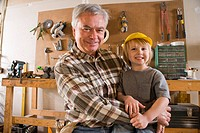 Portrait of happy grandfather and grandson in garage