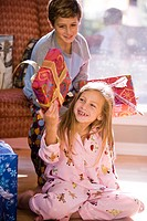 Portrait of bother and sister shaking Christmas gift on living room floor