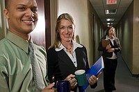Portrait of three multi_ethnic businesspeople standing office corridor, with coffee mugs