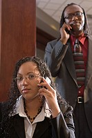 Portrait of two multi_ethnic businesspeople using mobile phone in office, focus on woman in foreground