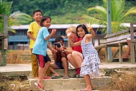 A group of Iban Dayak children with a tourist and camera outside their longhouse on the Rajang River near Kapit in Sarawak, northwest Borneo, Malaysia...