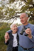 Senior couple standing with arm around, holding binoculars