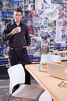 Portrait of young man holding cup in office with posters in background