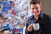 Portrait of young man holding coffee cup in front of bulletin board covered with photos