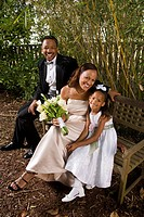 Portrait of happy African American bride and groom in outside nature setting with flower girl