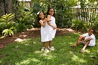Portrait of happy elementary age African American children playing outside in garden area