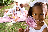 Close_up portrait of happy African American girl holding flower close to face with family in the background