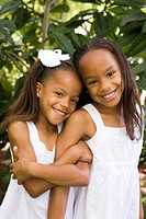 Outdoor portrait of happy African American girls, arms latched