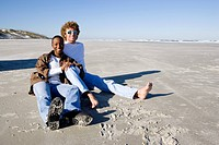 Portrait of young interracial couple sitting in sand at beach