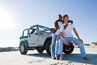 Young interracial couple sitting near Jeep, woman embracing man