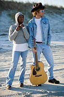 Young interracial couple standing with guitar on beach