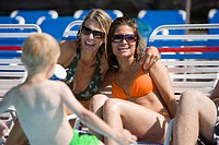 Closeup of two women in swimsuits on lounge chairs sitting with family