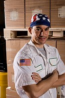 Portrait of worker standing in storage warehouse next to cardboard boxes