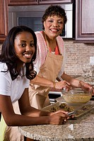 Side view of mother/grandmother and teenage daughter baking cookies in kitchen