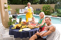 Portrait of three_generation family sitting by swimming pool