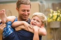Father playfully hugging young son