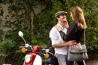 Young couple embracing next to motor scooter