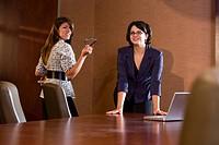 Two business women in conference room, opening door