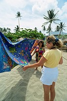 Tourist choosing tablecloth, Turtle Beach, Tobago, West Indies, Caribbean, Central America