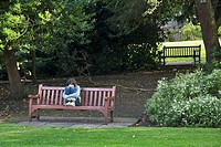 Lone girl sitting on bench in St Mary's park, York. Yorkshire, England, UK