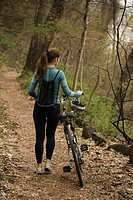 Young woman walking with bicycle through forest