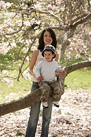 Portrait of mother and son sitting on tree trunk outdoors