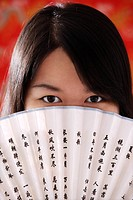 Chinese woman looking over hand_held fan with Chinese characters