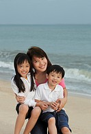 Young woman hugging boy and girl on beach