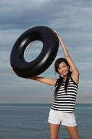 Young woman smiling and holding up inner tube