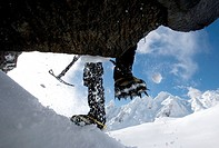 Mountaineer climbing snow covered mountain with crampons and ice axe