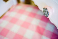 Detail pink drawer knob over pink gingham chair cushion