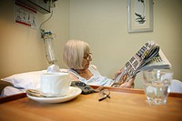 Elderly woman patient reading a newspaper in hospital bed.