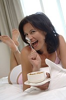 Woman with cereals in bed