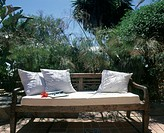 wooden bench with white cushions
