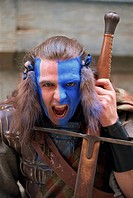 Head and shoulders portrait of Braveheart, Highlander man in leather costume with facial paint of blue and white, snarling at the camera, Edinburgh, L...