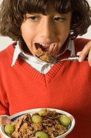 Young boy eating a healthy cereal with grapes.