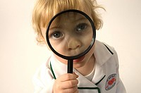 Young boy dressed as a doctor looking through a magnifying glass.