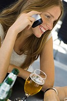 Young woman sitting at outdoor cafe, using cell phone