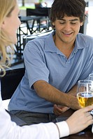 Young man sitting at outdoor cafe with friend