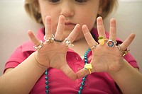 Little girl wearing several plastic rings on fingers, close-up