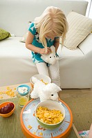 Little girl feeding cereal to stuffed toy