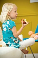 Little girl eating apple on sofa, side view