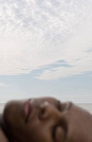 Man sleeping near ocean, blurred face in foreground, focus on sky